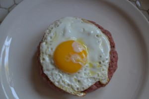 A grass fed angus cake topped with a farm fresh egg
